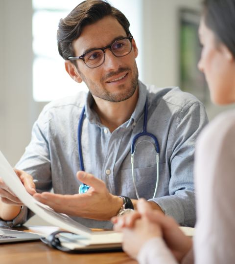 UK GP holding appointment with patient (OnMedica homepage)